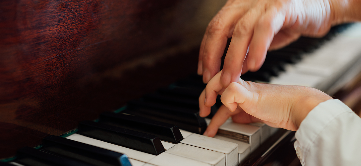 Piano keyboard student and teacher's hands