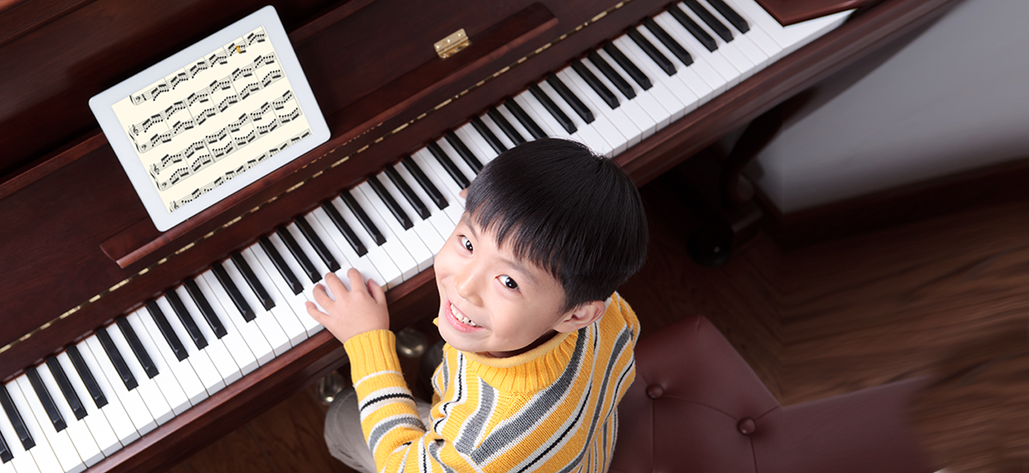 Happy Student Sitting at a Piano